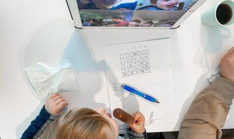 Gutt ovenfra med bingobrett på videochat med familie